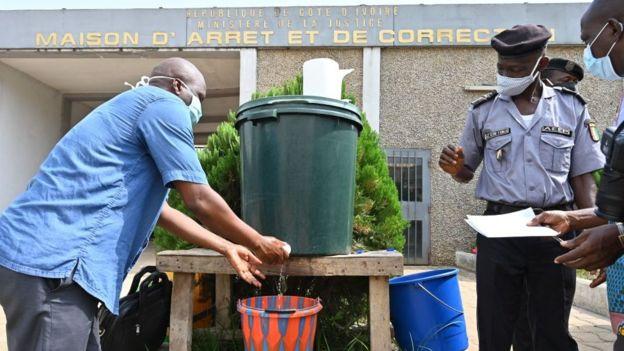 Un homme se lave les mains à l'entrée de la prison centrale d'Abidjan